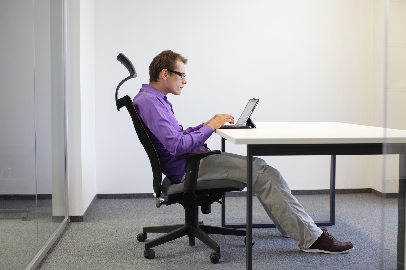 text neck - man in slouching position on ergonomic chair working with tablet at desk